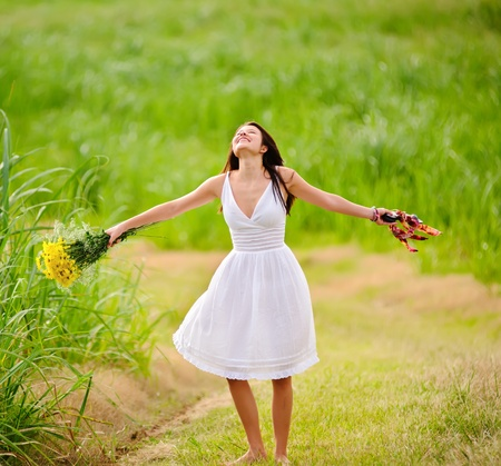 Happy woman is free and enjoys the spring sunlight