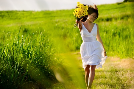 Photo pour Candid skipping carefree adorable woman in field with flowers at summer sunset. - image libre de droit