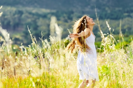 Photo for beautiful girl laughs and dances outdoors in a meadow durning sunset - Royalty Free Image