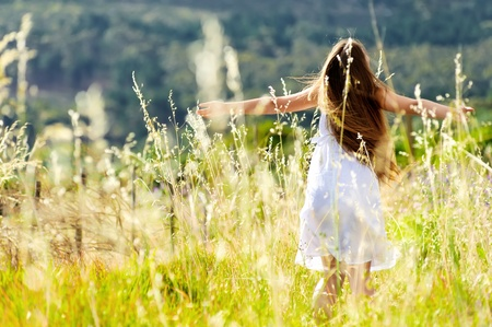 Foto de beautiful girl laughs and dances outdoors in a meadow durning sunset - Imagen libre de derechos