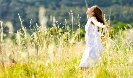 Photo pour beautiful girl laughs and dances outdoors in a meadow durning sunset - image libre de droit