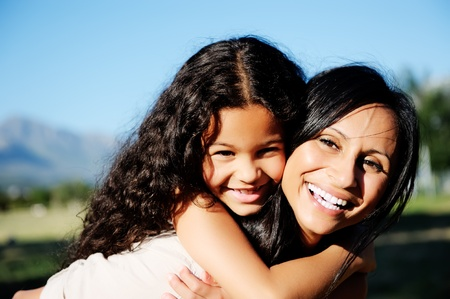 mom and daughter have fun outdoors, smiling and piggyback in the sunshine