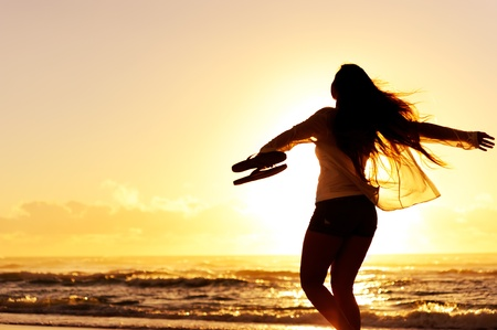Photo pour carefree woman dancing in the sunset on the beach. vacation vitality healthy living concept - image libre de droit