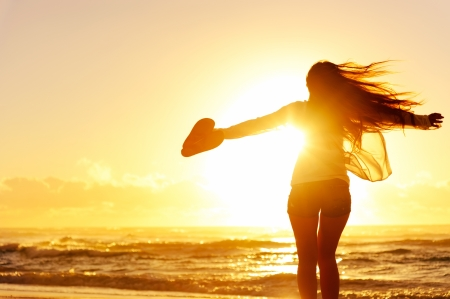 Foto de carefree woman dancing in the sunset on the beach. vacation vitality healthy living concept - Imagen libre de derechos