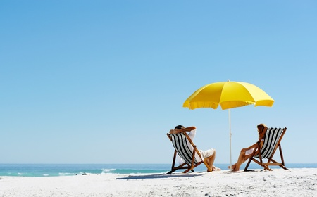 Photo pour Beach summer couple on island vacation holiday relax in the sun on their deck chairs under a yellow umbrella. Idyllic travel background. - image libre de droit
