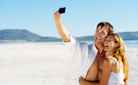Foto de young couple pose for a self portrait at the beach, laughing and having summer fun together - Imagen libre de derechos