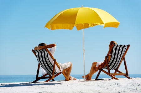 Foto de Beach summer couple on island vacation holiday relax in the sun on their deck chairs under a yellow umbrella. Idyllic travel background. - Imagen libre de derechos