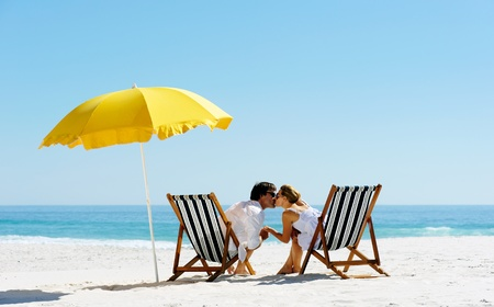 Foto de Beach summer couple kissing on island vacation holiday in the sun on their deck chairs under a yellow umbrella. Idyllic travel background. - Imagen libre de derechos