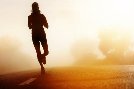 Foto de Runner athlete feet running on road  woman fitness silhouette sunrise jog workout wellness concept  - Imagen libre de derechos