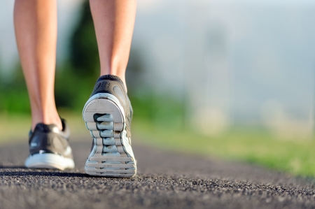 Foto per feet of an athlete running on a park pathway training for fitness and healthy lifestyle - Immagine Royalty Free