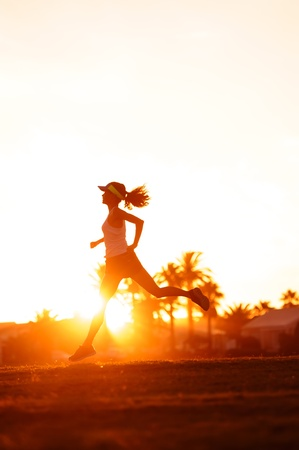 Photo pour silhouette of a woman athlete running at sunset or sunrise. fitness training of marathon runner. - image libre de droit
