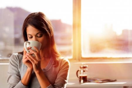 Foto de woman enjoys fresh coffee in the morning with sunrise at home lifestyle - Imagen libre de derechos
