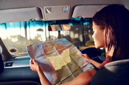 Photo pour Woman on vacation looking at map for directions while driving in car - image libre de droit