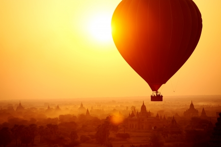 Photo for Silhouette of hot air balloon over Bagan in Myanmar, tourists watching sunrise over ancient city - Royalty Free Image