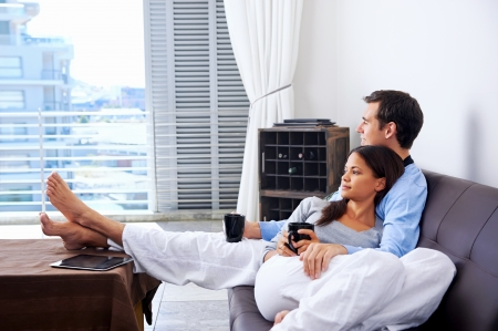 Foto de Couple relax at home with cup of coffee and sofa couch. happy healthy relationship - Imagen libre de derechos