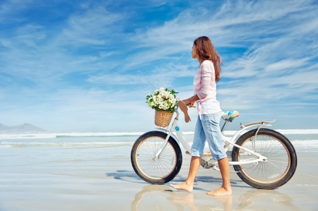 Photo pour Woman with bike at the beach - image libre de droit