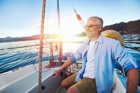 Foto de successful retired man sailing portrait at sunrise on boat - Imagen libre de derechos