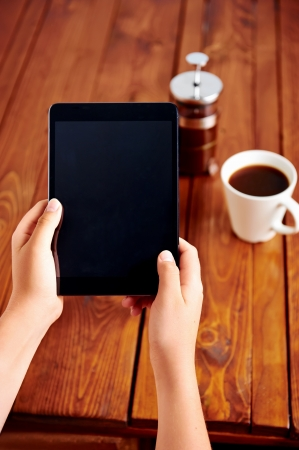 Photo for Young woman uses tablet while relaxing at home with coffee on the sofa couch - Royalty Free Image