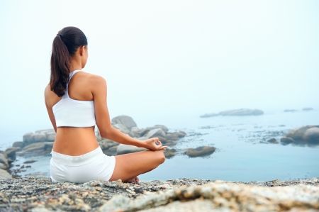 Foto de yoga beach woman doing pose at the ocean for zen health and peaceful lifestyle - Imagen libre de derechos