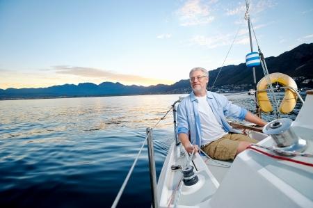 Foto de carefree happy sailing man portrait of mature retired man on ocean boat at sunrise - Imagen libre de derechos