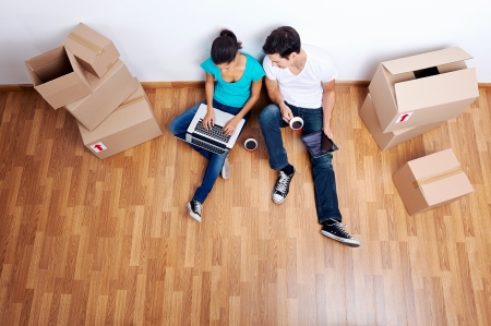 Photo pour overhead view of couple sitting on floor together using computer wireless internet while moving into new home - image libre de droit