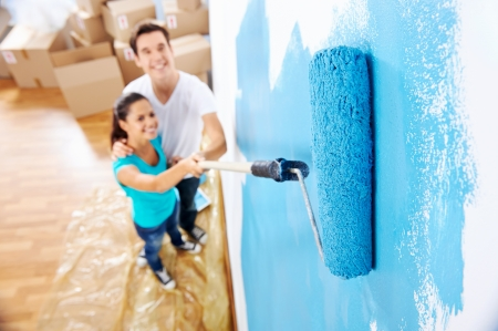 Photo for overhead view of couple having fun renovating their new home together with blue paint on a roller - Royalty Free Image