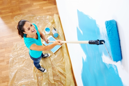 Photo pour overhead view of woman painging new apartment standing on wooden floor - image libre de droit