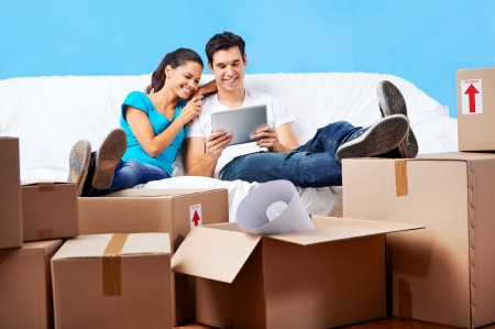 Foto de couple moving in together relaxing on sofa couch with laptop tablet computer and boxes - Imagen libre de derechos