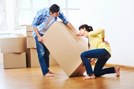 Photo for back injury from carrying heavy box while moving home - Royalty Free Image