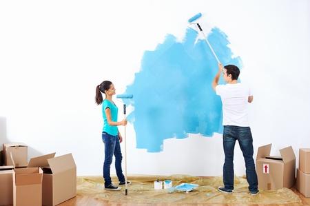 Foto de couple painting new home together with blue color happy and carefree relationship - Imagen libre de derechos