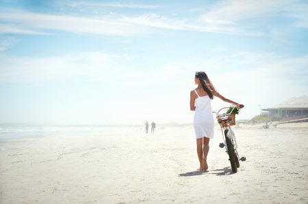Photo pour Woman walking with bicycle along beach sand summer lifestyle carefree - image libre de droit