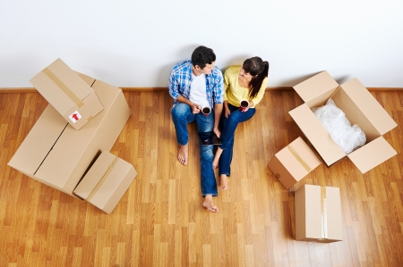 Photo pour overhead view of couple moving in to new home and using wireless internet on tablet computer - image libre de droit