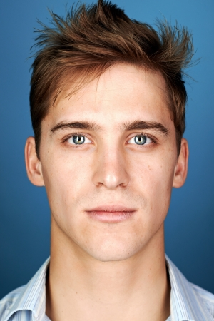 Photo pour portrait of real man face looking at camera on blue background - image libre de droit