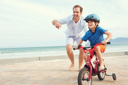Foto de Father and son learning to ride a bicycle at the beach having fun together - Imagen libre de derechos