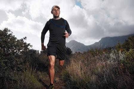 Foto de Ultra marathon trail runner with determination exercising for fitness and healthy lifestyle - Imagen libre de derechos