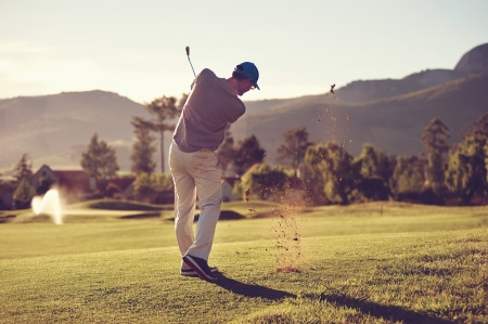 Foto de Golfer hitting golf shot with club on course while on summer vacation - Imagen libre de derechos