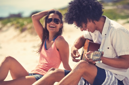 Photo for Cute hispanic couple playing guitar serenading on beach in love and embrace - Royalty Free Image