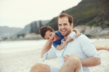 Photo for Fatehr and son playing at beach together portrait fun happy lifestyle - Royalty Free Image