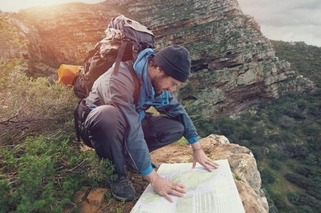 Photo pour Lost hiker with backpack checks map to find directions in wilderness area - image libre de droit