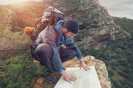 Foto de Lost hiker with backpack checks map to find directions in wilderness area - Imagen libre de derechos