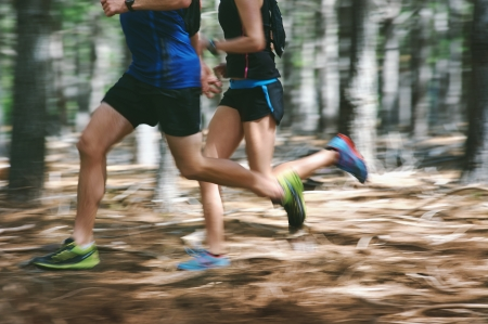 Photo pour Couple running fast through the forest on trail run with motion blur - image libre de droit