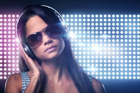 Photo for Portrait of woman dj enjoying music on headphones and nightclub lights - Royalty Free Image