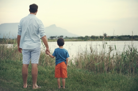 Photo for Father and son holding hands looking out over the lake at the mountain at sunset - Royalty Free Image