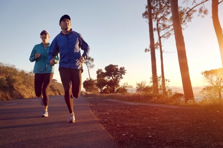 Photo pour Running at sunrise couple exercising for marathon and workout fitness - image libre de droit