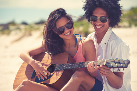 Photo pour Cute hispanic couple playing guitar serenading on beach in love and embrace - image libre de droit