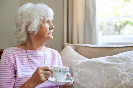 Photo for A mature woman  holding a cup and saucer while looking out the window with copyspace - Royalty Free Image