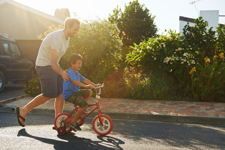 Photo for young boy learning to ride bicycle as father teaches him in the suburb street having fun. - Royalty Free Image