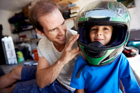 Foto de portrait of young boy playing with fathers motorbike helmet and helping his dad with fixing a motorcycle in the garage - Imagen libre de derechos