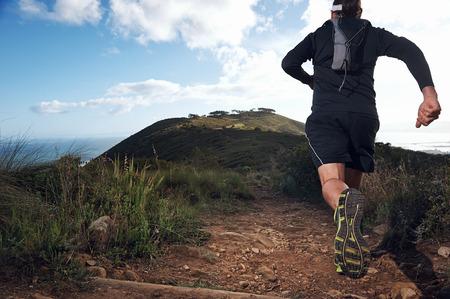 Foto de trail running man on mountain path exercising - Imagen libre de derechos