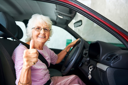 Photo for An positive older woman sitting in a car showing a thumbs up - Royalty Free Image